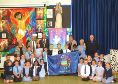 The Deputy Lord Mayor of the City and County of Swansea and his wife, Mike Hedges AM, Pam Evans Founder of Peace Mala, Father Keith Evans and Norma Glass MBE with Year 3 Peace Mala Ambassadors