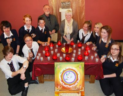 Mr Ricky Perrott, Sr Anne Reddington RSM and pupils of St John Lloyd Catholic Comprehensive School, with the pilgrimage mandala and some of the peace votives, in the school chapel