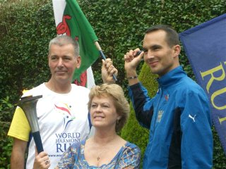 Pam Evans holding the World Harmony Runners' peace torch