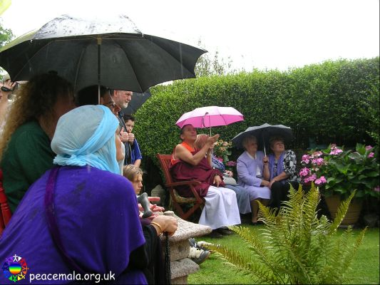 Guests in the Peace Garden watching the hoop dance, as it starts to rain