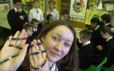 Peace Mala making at Coedcae school with Amy Rees displaying the bracelets